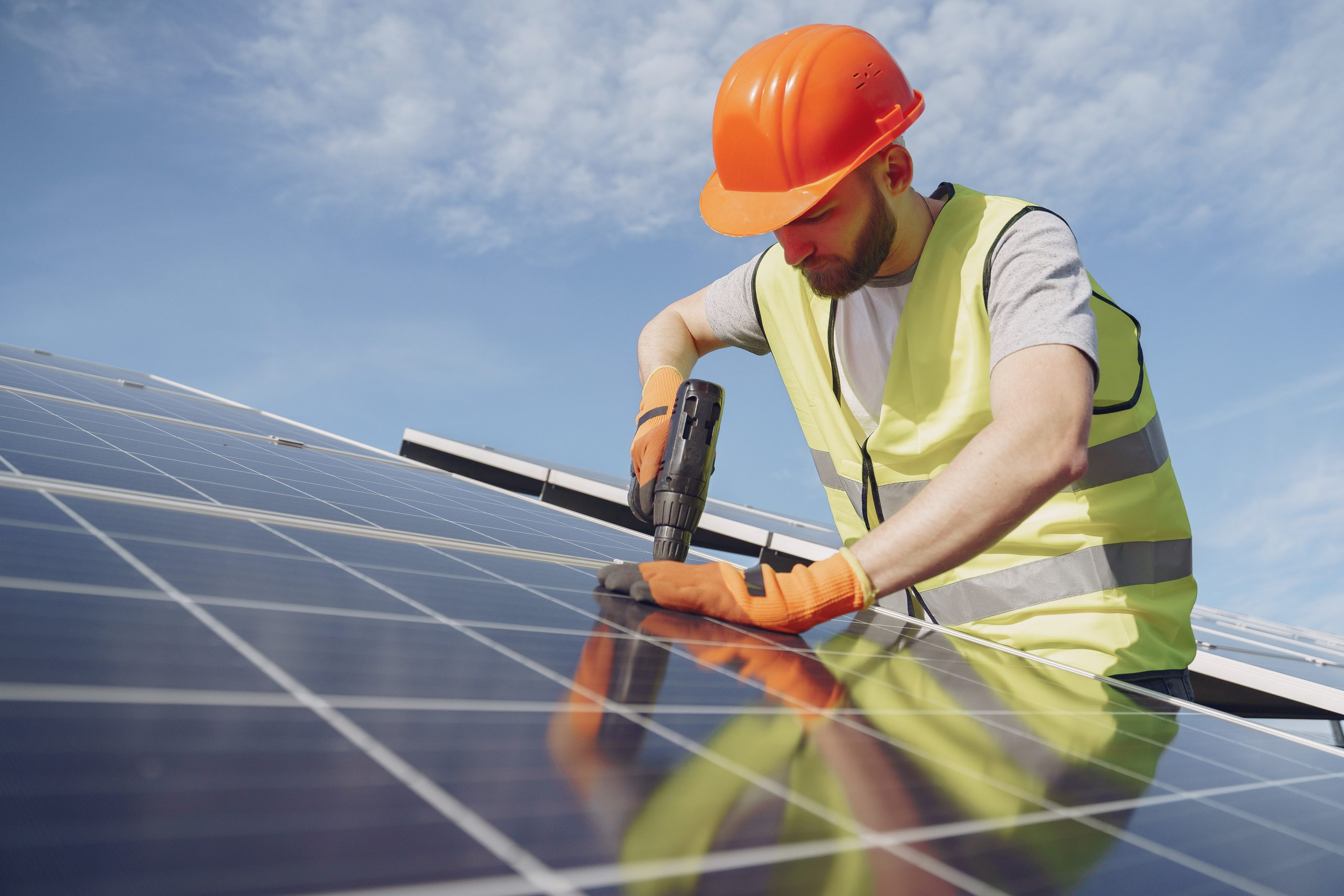 Male worker with solar batteries. Man in a protective helmet. Installing stand-alone solar panel system.
